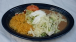 Burrito Real - Beef burrito topped with lettuce, sour cream and tomatoes. Served with rice and beans.